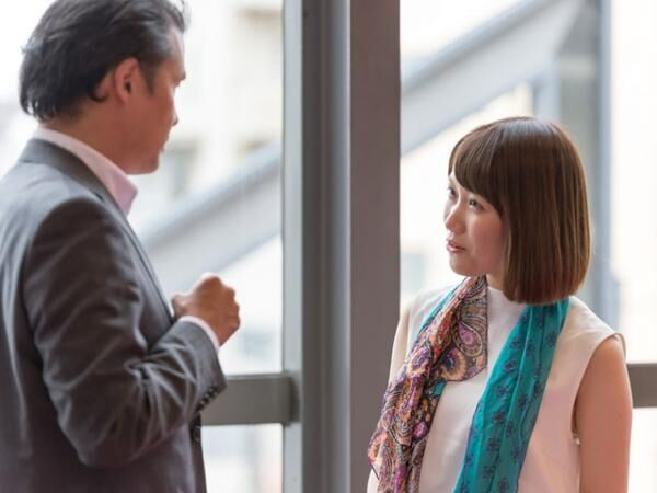 Japanese businessman and young woman are talking