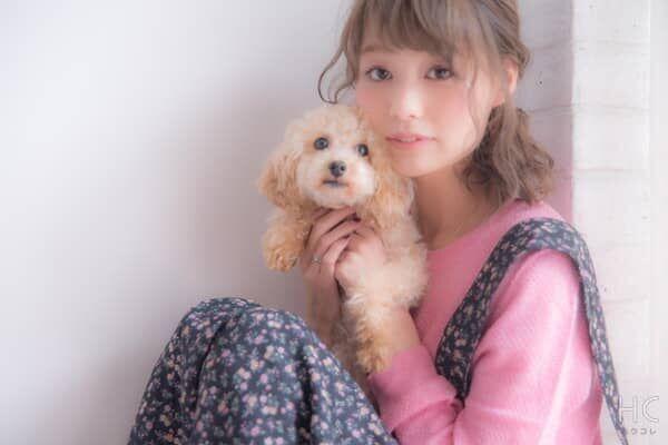 犬を抱いたピンクの服の女性