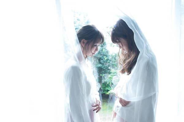 カーテンに隠れる二人の女性