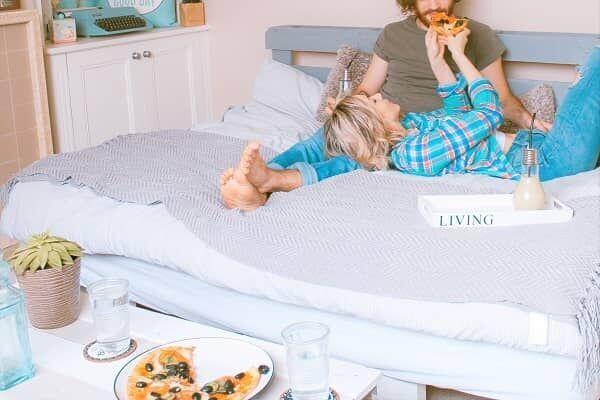 ベッドの上でイチャイチャピザを食べるカップル