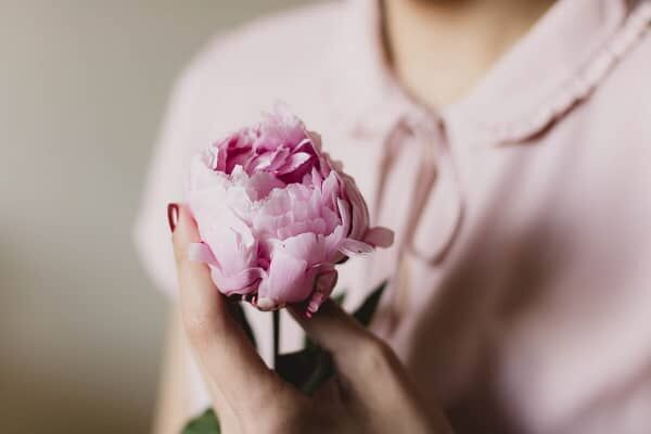 花を胸の前で持つ女性