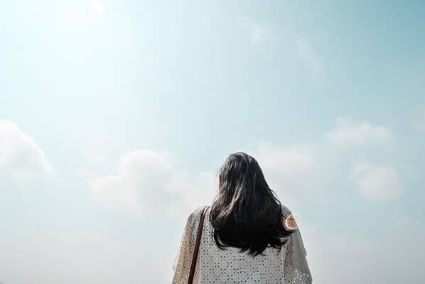 空と女性の後ろ姿