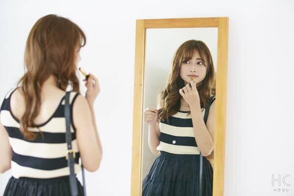 鏡を見て化粧する女性