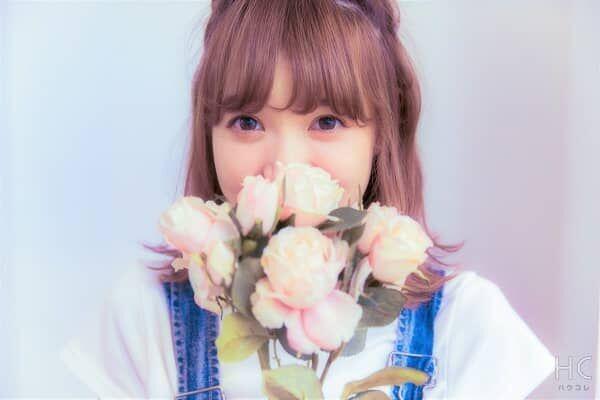 顔の前で花を持つ彼女
