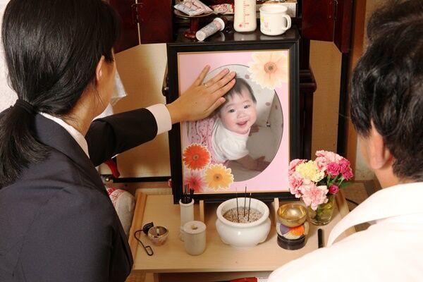 自宅で愛美利ちゃんの遺影をなでる母・B子さん。