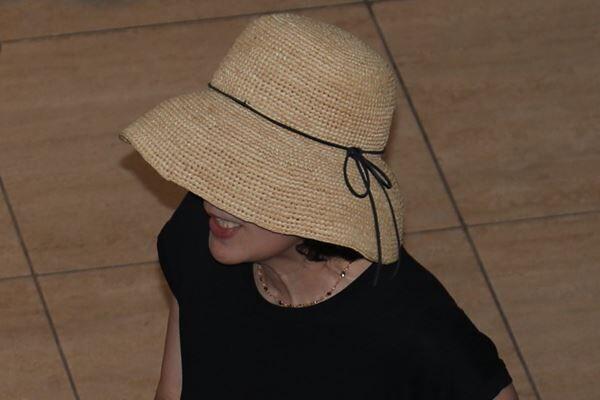 麦わら帽子を深くかぶって警戒した様子の高畑淳子。