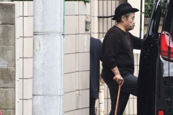 10月下旬、杖をつきながら送迎車に乗り込み仕事場に向かう西田。