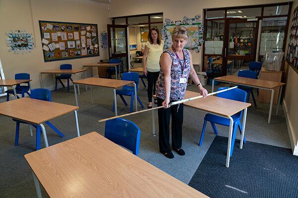 学校再開を前に、机同士の距離を測る教師(写真:AP/アフロ)