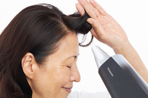 前髪をつまんで立ち上げ、ドライヤーの風を当てて乾かすと、付け根が立ち上がる