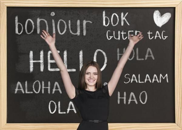 Woman near words hello in different languages on chalkboard