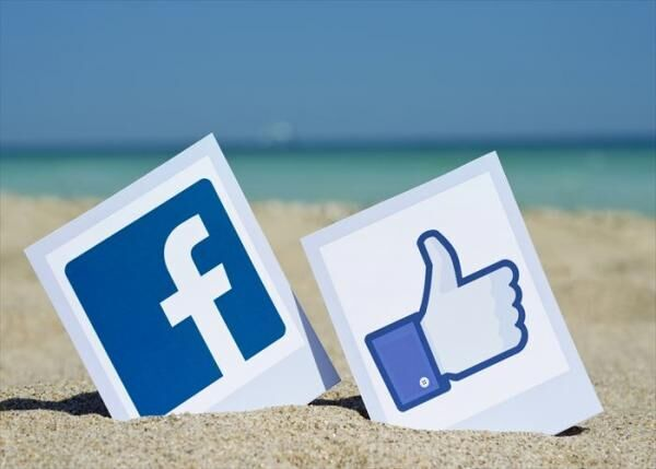 KIEV, UKRAINE - AUGUST 10, 2015: Facebook like logos for e-business, web sites, mobile applications, banners, printed on paper and placed in the sand against the sea Social network facebook sign.