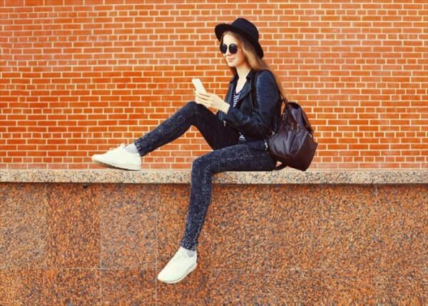 Fashion pretty woman using smartphone in rock black style over bricks textured background