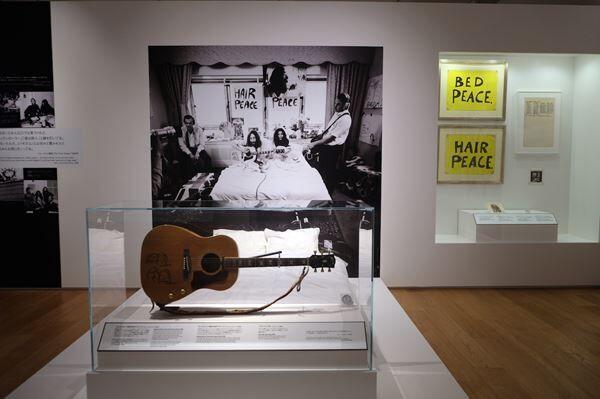 1969年にふたりが行った平和運動「ベッド・イン」を再現。ジョンがベッドに持ち込んだギブソンのギターにはふたりの自画像が描かれている