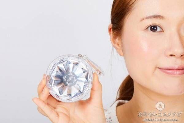 顔の横に『ジルスチュアートブルーム ミックスブラッシュコンパクト』のコンパクトケースを持つ女性