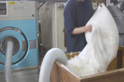 集めた羽毛を洗濯機にバキュームダクトを使って移動させます