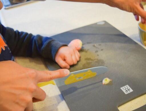 左手をグーに握って「こう切るんだよ」と教えながら野菜を切る