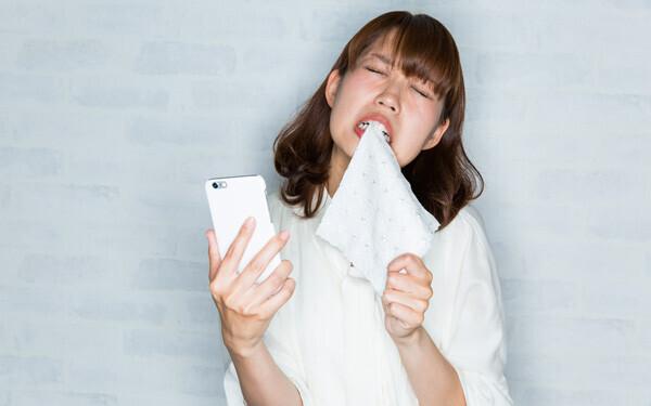 スマートフォン / 悔しがる女性