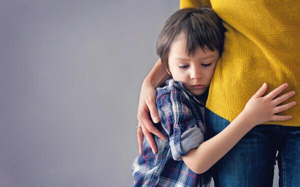 不安で母親の腰にすがりつく少年