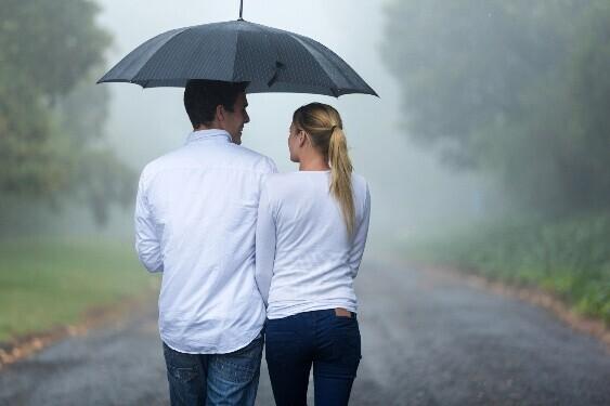 ひとつの傘に入る男女