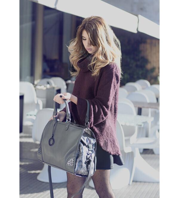 秋色のニットを来ている女性。もっているバッグの中身をのぞいている。