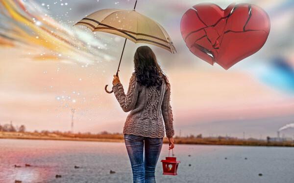 傘をさして水辺に佇む女性