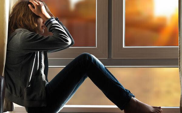 窓辺で頭を抱える女性