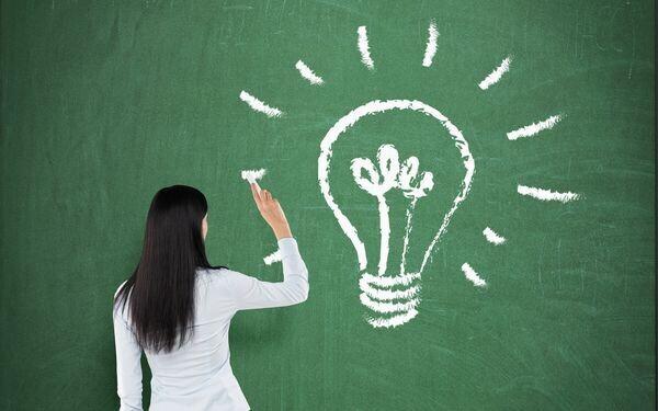 黒板に電球を描く女性
