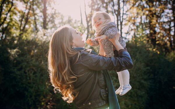 子どもを抱きあげる母親