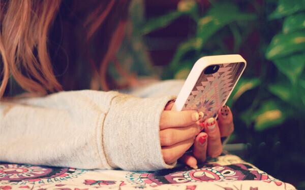 iPhoneを触りながら、LINEの返信をまつ若い女性