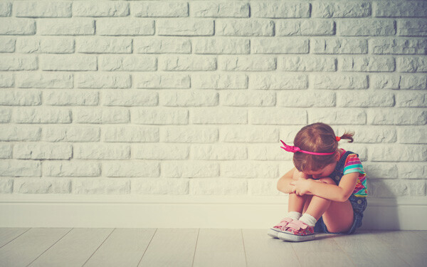 壁を背にして、膝を抱えて泣く女の子