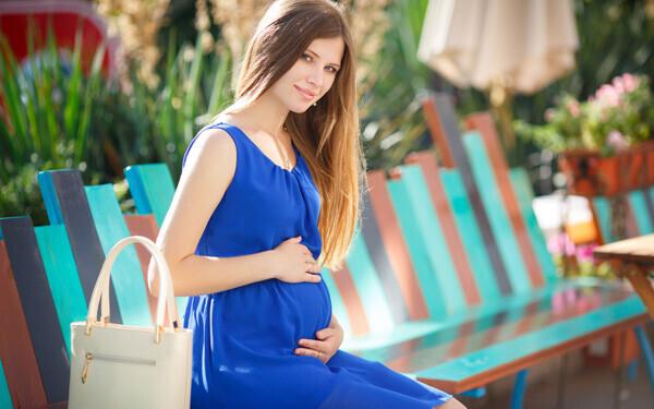 ベンチに腰掛け、こちらを向いて微笑む妊婦さん