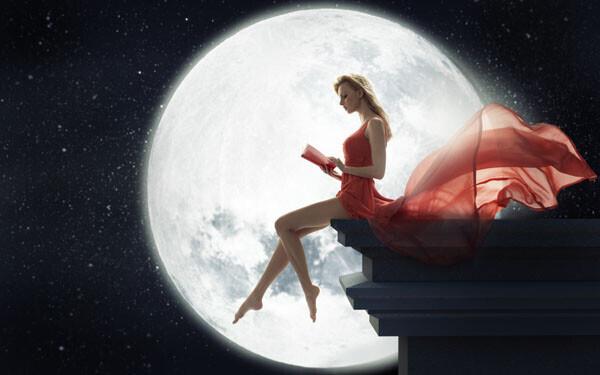 月夜に屋根で本を読む女性