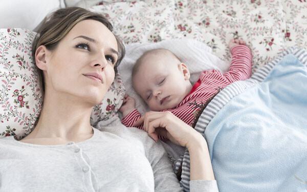 寝ている赤ちゃんと疲れているママ