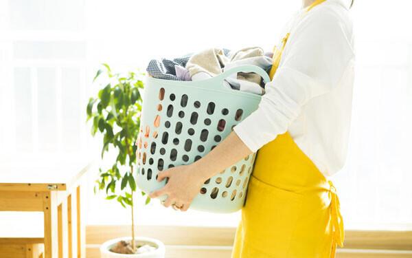 洗濯ものをとり込む黄色いエプロンの女性