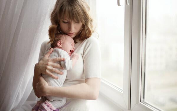 窓辺で赤ちゃんを抱くママ