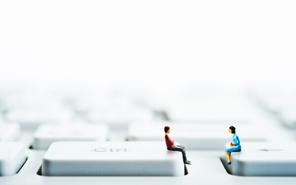パソコンのキーボードの上に座っている男女