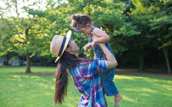 夏の公園で日差しを浴びながら遊ぶ親子
