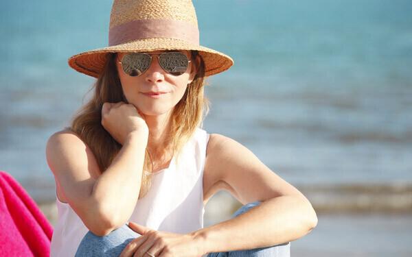 海辺でサングラスをかけ麦わら帽子をかぶる女性