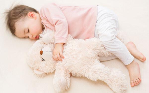 ぬいぐるみを抱いて眠る赤ちゃん
