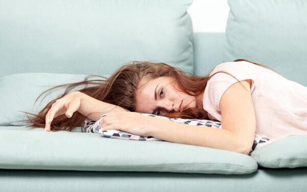 ソファーでぐったり寝そべる女性