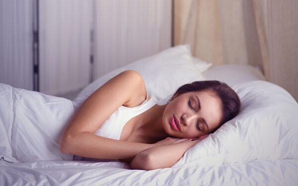 目を閉じてベッドに横たわる女性