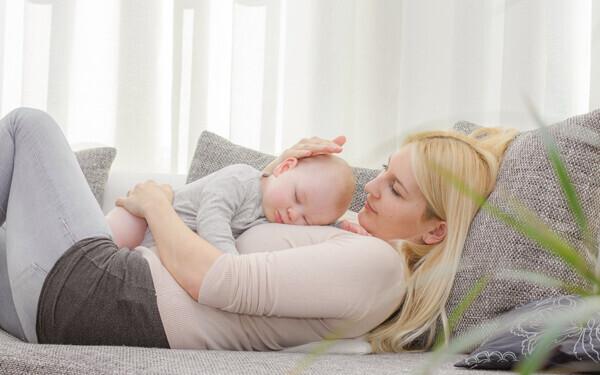 赤ちゃんを抱いてソファに横たわるママ