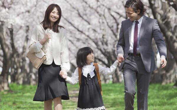 桜の下を歩く家族