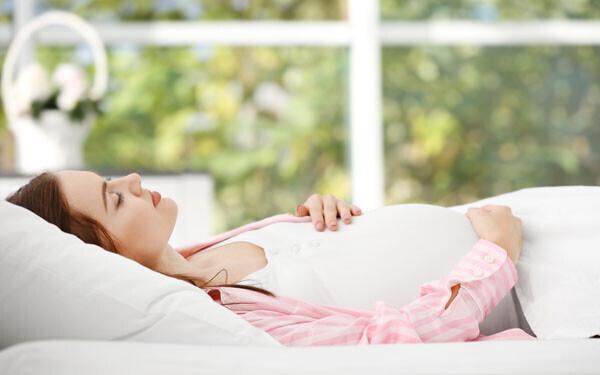 ベッドに横たわる妊娠初期の女性