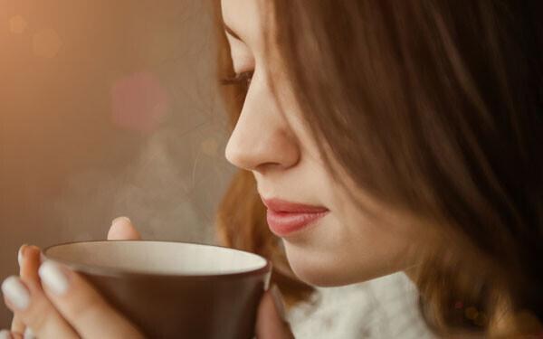 温かい飲み物を飲んでいる女性