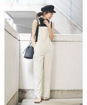 黒のノースリーブのハイネックTシャツに白のサロペットを合わせた女性
