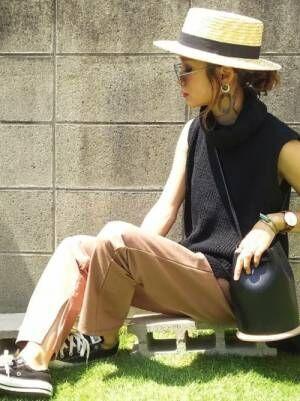 黒のノースリーブのタートルネックニットにベージュのパンツを合わせて、大ぶりのイヤーアクセサリーをした女性