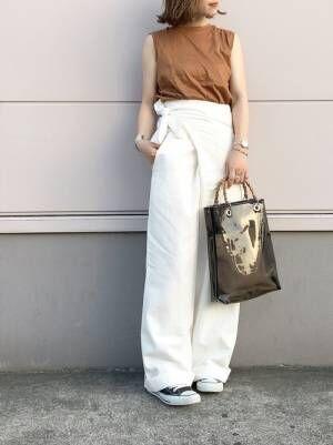 ブラウンの首が詰まったタンクトップに白のワイドパンツを合わせて、ブラウンのクリアバッグを持った女性