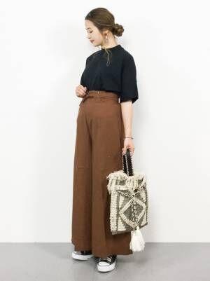 黒のハイネックTシャツにブラウンのワイドパンツを合わせた女性