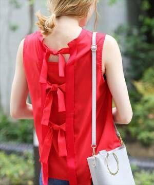 バックリボンのディテールの赤いハイネックブラウスを着た女性